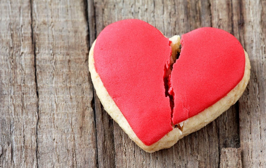 Cracked heart shaped cookie decorated with red icing as a concept of broken heart, breakup and end of relationship